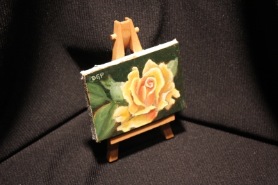 orange yellow rose painting on easel